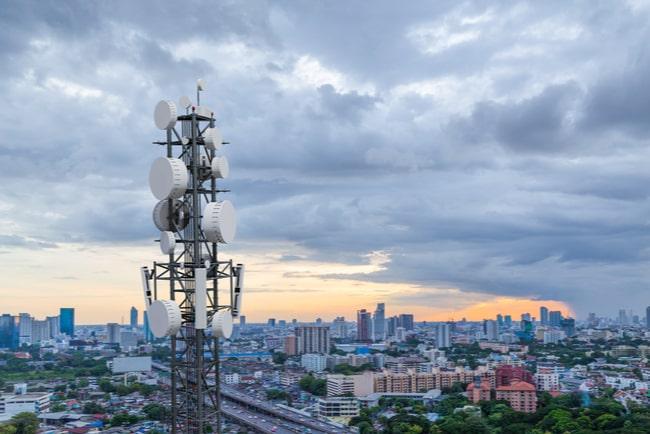 5G-mast med storstad i bakgrunden
