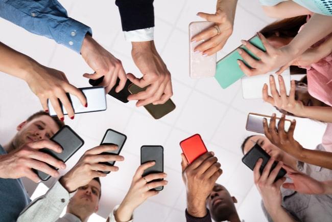 grupp av människor står i en ring och använder smartphones