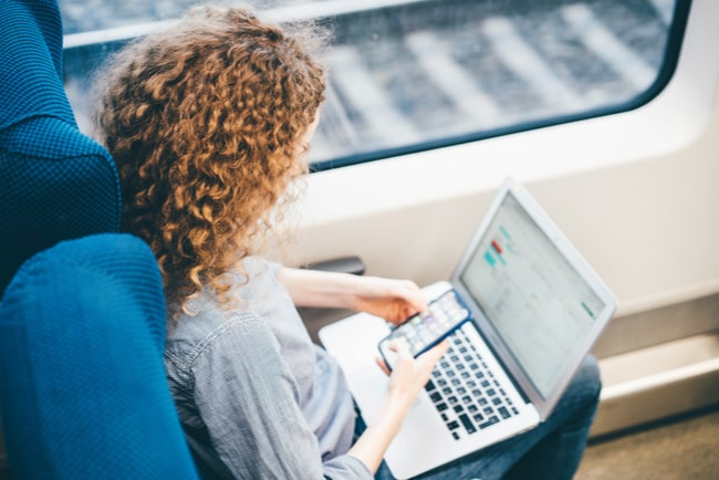 kvinna med smartphone och laptop på tåg