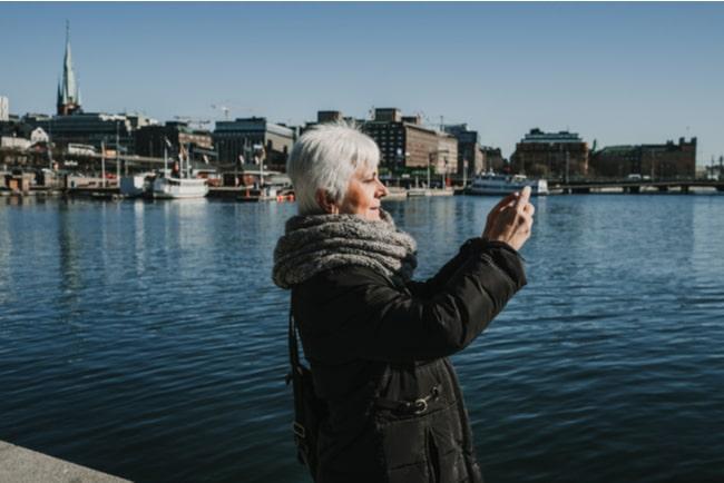 Medelålders kvinna med mobiltelefon vid vatten i Stockholm,