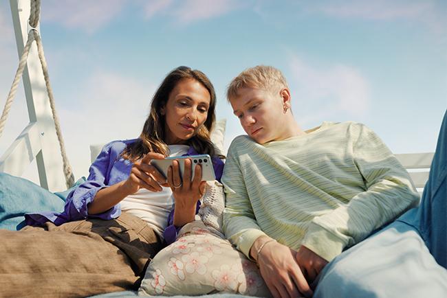 mor och son tittar på mobil i solen