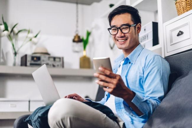 leende man i soffa med dator i knät och telefon i handen
