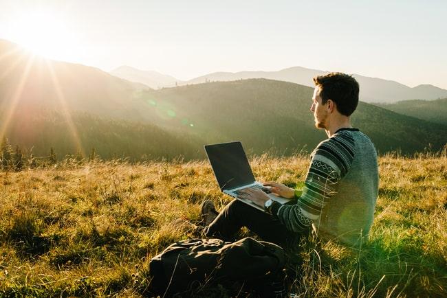 man sitter i naturlandskap med laptop i knät
