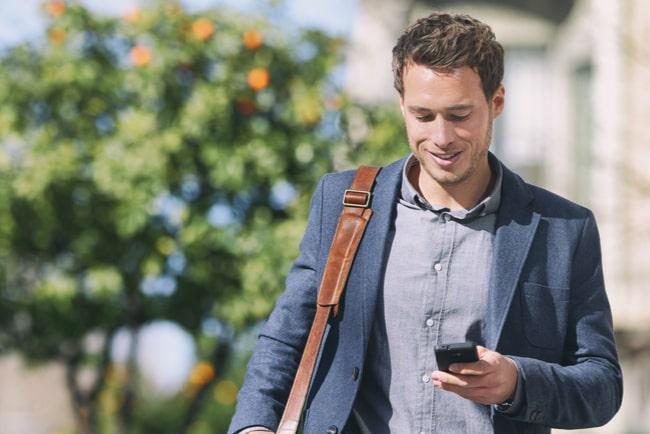 leende man med mobil med träd och byggnad i bakgrunden