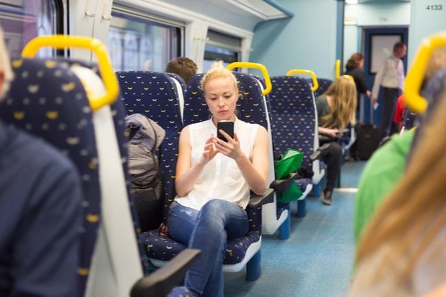 kvinna använder mobiltelefon på tåg med flera andra resenärer