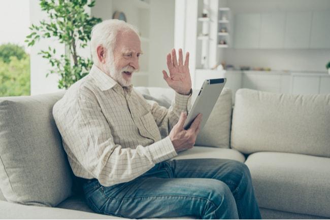 äldre man med surfplatta vinkar till någon på skärmen