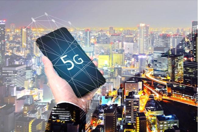 Hand håller i en mobiltelefon med 5G med en storstad i bakgrunden.