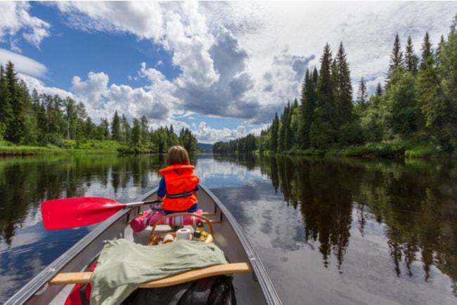 en pojke paddlar kanot på spegelblankt vatten
