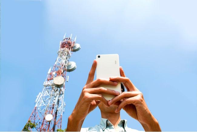 man håller mobil teletorn i bakgrunden mot blå himmel