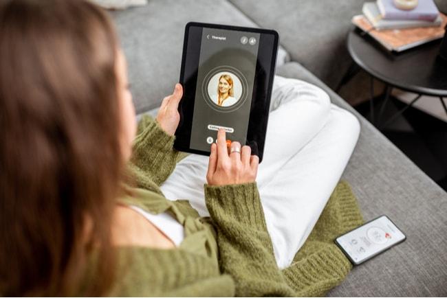 kvinna kontaktar vård genom videosamtal