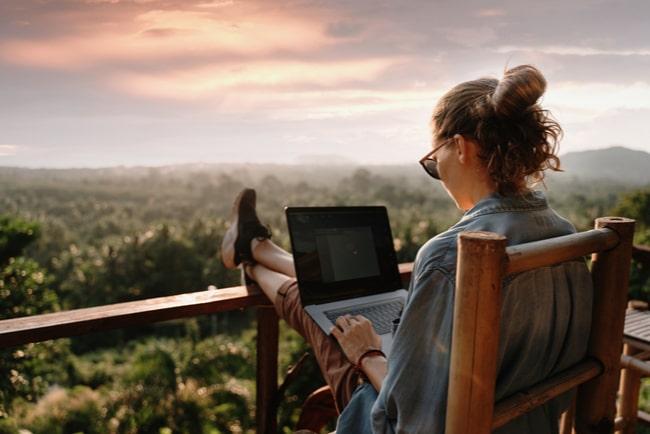 kvinna sitter med laptop på balkong