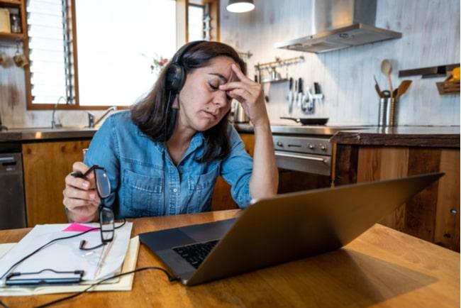 trött kvinna arbetar hemma framför laptop vid köksbordet